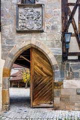 Fototapete - Wappen über Torbogen mit alter Holztür - Alte Hofhaltung in Bamberg