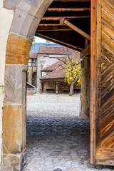 Fototapete - Torbogen mit alter Holztür - Alte Hofhaltung in Bamberg