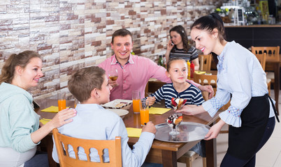 Polite pretty waitress serving dishes to family