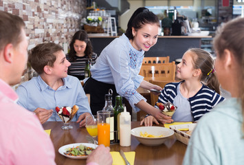Polite nice waitress serving dishes to family