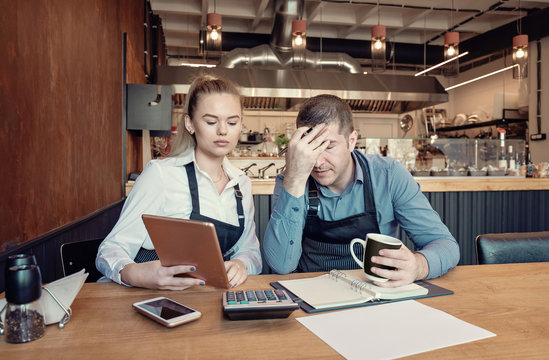 Depressed male and female entrepreneurs overwhelmed by finance problems - Nervous manager checking restaurant finance