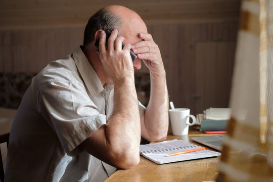 Senior man feeling upset having phone conversation depressed by hearing bad news