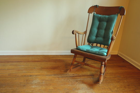 Old rocking chair in the corner of a room with old hardwood flooring.