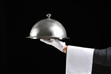 Hand of waiter with tray and cloche on dark background