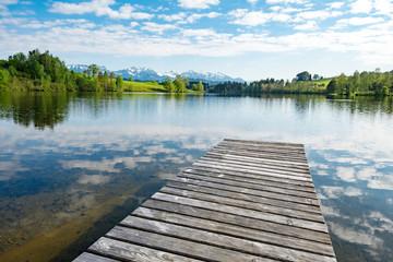 Holzsteg  führt in einen klaren Bergsee im Allgäu