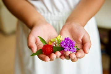 両手でお花を持ってきた女の子
