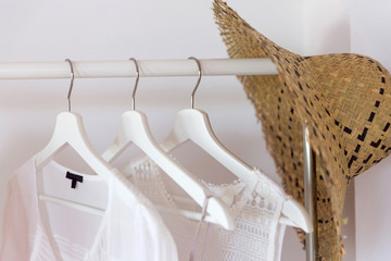 Clothing from eco organic cotton in trend colors and accessories hang on a hanger near a white wall