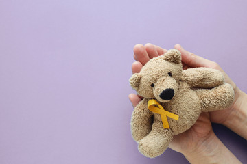 Hands holding children soft toy brown bear with yellow gold ribbon on purple background, Childhood cancer awareness