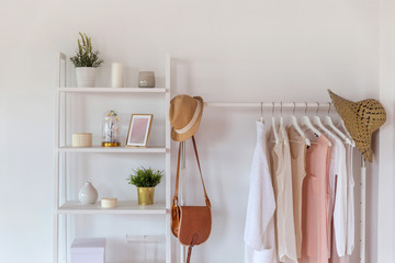Scandinavian style, clothes organic cotton in trendy colors on a hanger and interior items on shelves