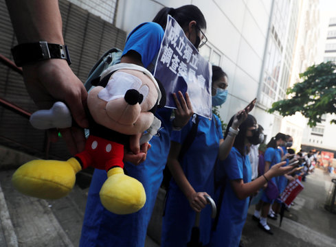Secondary school students hold a Mickey Mouse stuffed doll with an eye patch as they form a human chain during a protest against what they say is police brutality against protesters, after clashes at Wan Chai district in Hong Kong