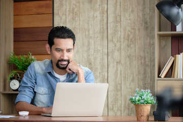 Handsome bearded guy is sitting at the working desk in his house using a laptop for work. Asian business entrepreneur checking the business profits happily.