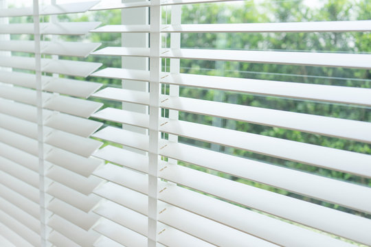 Close up view of window with horizontal blinds. White Roller Blinds or Louver curtains at the glass window