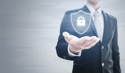 Businessman holding shield with security lock icon technology