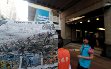 People take newspapers, with headlines and photos showing clashes between police and protesters on its front pages, in front of Wan Chai metro station in Hong Kong