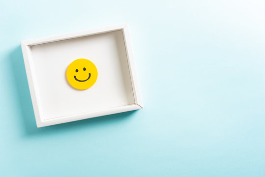 Concept of well done, feedback, employee recognition award. happy yellow smiling cartoon face frame on blue background with copy space.