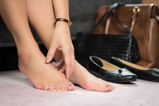 Closeup : Bare feet of working woman, she touching her toes to release pain after long day wearing pointy and narrow shoes  -  Medical condition called bunions (Hallux valgus) Woman's health concept.