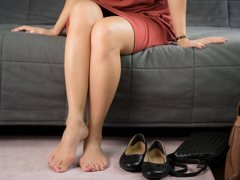 Closeup of a working woman's legs, she sitting on a couch taking off a black tight and narrow shoes which cause her painful and sore feet. Woman's feet problem, Bunions, Hallux valgus, Woman's health.