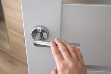 Female hand on metal door handle. Modern interior detail Wall mural