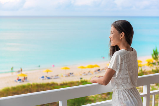 Resort vacation happy Asian woman tourist enjoying ocean view from beach front hotel room on Caribbean holidays.