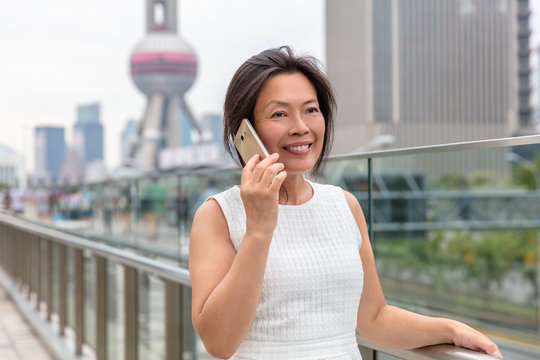 Phone Asian woman mature middle age chinese businesswoman talking business on mobile smartphone call outside on Shanghai street with Pearl tower in background. China travel.