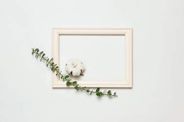 White wooden photo frame and spring green twigs of plants on gray background. Flat lay top view copy space. Stylish minimal composition, artwork mockup, picture frame, home decoration