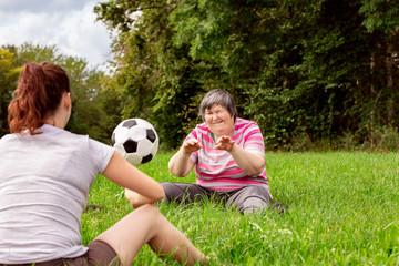 Zwei geistig behinderte Frauen werfen sich einen Ball zu, Übungen für Koordination und Konzentration