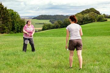 Freizeit und Pädagogik für behinderte Menschen, zwei Frauen spielen Federball auf einer Wiese
