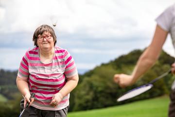 Frau mit geistiger Behinderung spielt Federball, Spiel und Spaß als palliative Therapie