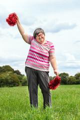 Geistig behinderte Frau tanzt mit Pom Poms auf der Wiese, Freizeitgestaltung