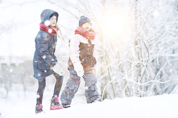 two sisters girls  winter for a walk / young girlfriends playing in the snow in the frost. The...