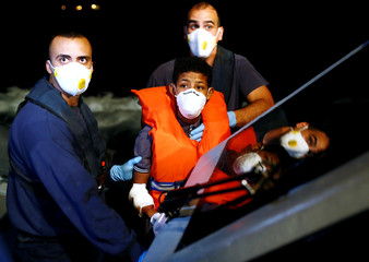 A Tunisian migrant is assisted by Armed Forces of Malta sailors during his medical evacuation to Malta from the German NGO Sea-Eye migrant rescue ship 'Alan Kurdi' in international waters off Malta in the central Mediterranean Sea