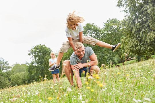 Kinder beim Bockspringen mit seinem Vater
