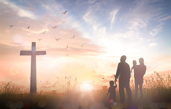 Surrender concept: Silhouette people looking for the cross on autumn sunrise background