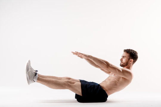 young man with a beard of a sports physique does an exercise on the muscles of the abdominal cavity on a white isolated background, the athlete goes in for sports, exercise on the muscles of the press