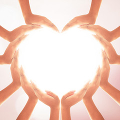 International human solidarity day concept: Human hands in shape of heart on blurred natural background
