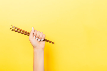 Cropped image of female hand holding chopsticks in fist on yellow background. Asian food concept with copy space Wall mural