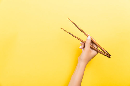 Female hand with chopsticks on yellow background. Traditional asian food with emty space for your design
