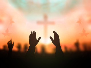 Worship God concept: human rising hands over blurred cross background