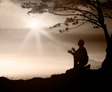 Pray concept: Humble man kneeling to praise and worship God on mountain sunset background