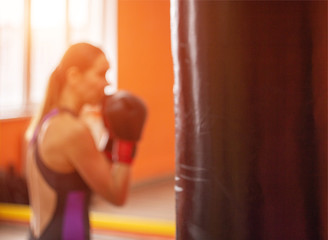 Cute girl boxer trains in the gym and hits the punching bag, sunset, bluured