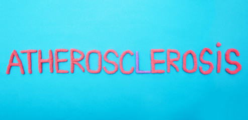 Atherosclerosis inscription in red letters on a blue background concept of vascular disease, background