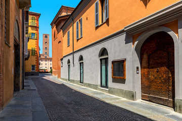 Narrow,cobblestone street among old colorful houses in Alba, Italy.