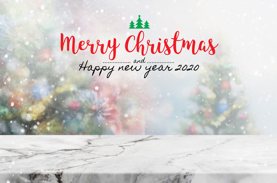 Christmas and Happy new year 2020 on empty marble stone table top on blur bokeh christmas tree background with snowfall - can be used for display or montage your products.