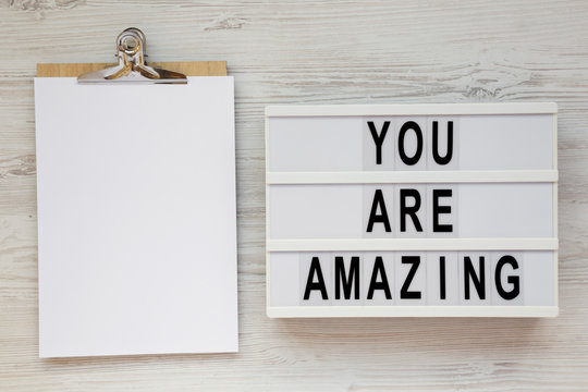 'You are amazing' words on a modern board, clipboard with blank sheet of paper on a white wooden background, overhead view. Top view, from above. Flat lay. Copy space.