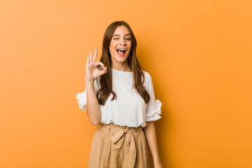 Young caucasian woman winks an eye and holds an okay gesture with hand. Wall mural