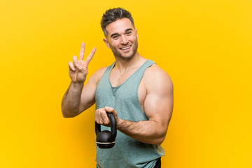 Caucasian man holding a bumbbell showing victory sign and smiling broadly.