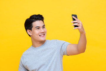 Young smiling handsome Asian man taking a selfie with cellphone