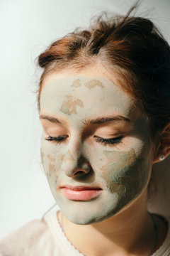 Clay mask on young woman, isolated on white background, close up