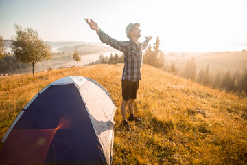 Happy hiking travel on top of mountain hand up looking to sunrise. Camp travel concept Wall mural