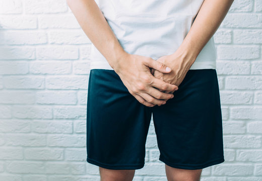 man wearing shorts holding genitals. Men's health, venereologist, sexual disease